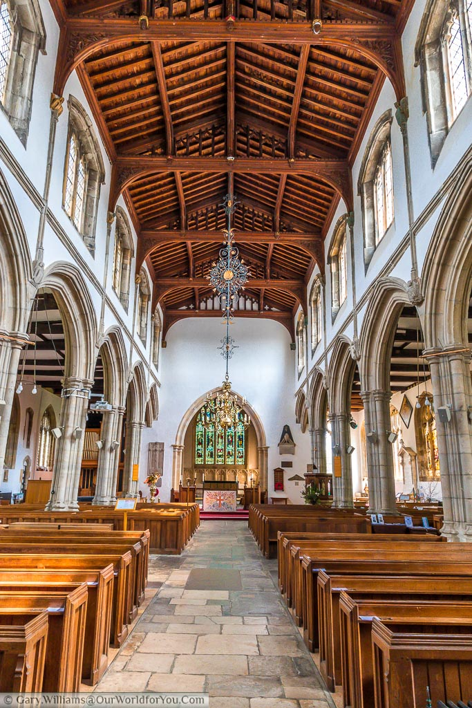 Inside the simple interior of St Dunstan's church.  The high vaulted wooden roof catches your eye as you look alone the path between the pews