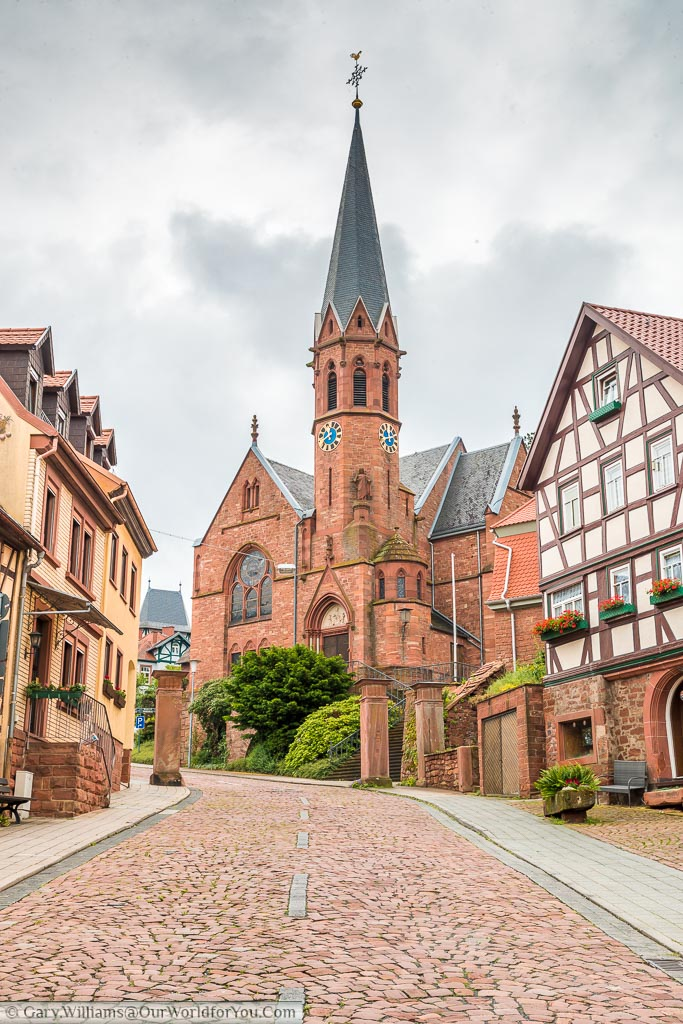 Looking up a cobbled street towards the red brick  Johannes church incorporating a narrow Bell tower.