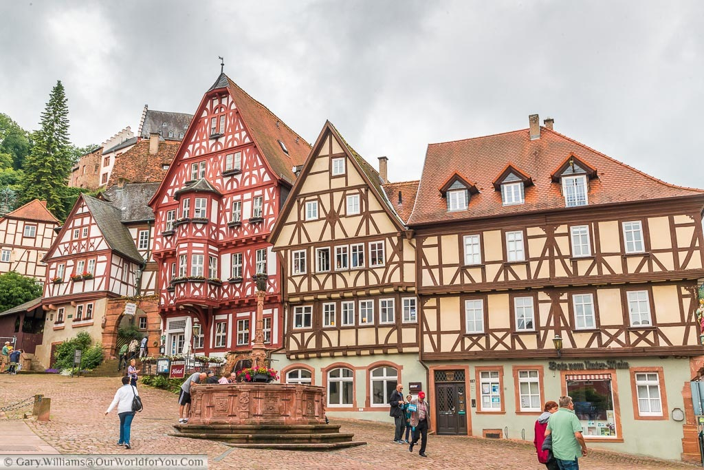 A red stone fountain in the centre of marktplatz surrounded by half-timbered traditional Bavarian buildings.