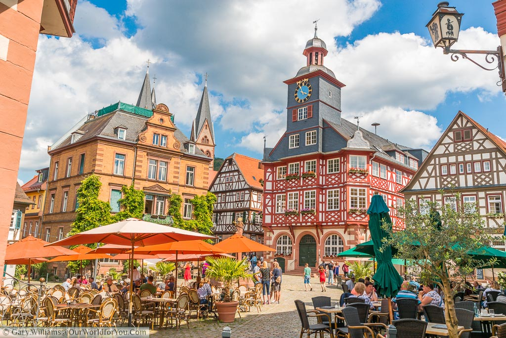 The bustling marktplatz, the centre of the Old Town of Heppenheim.  Around the edges of the square tables and chairs under parasols for the local cafes and bars. In the background is the town Hall another half-timbered building with a tiled clocktower.