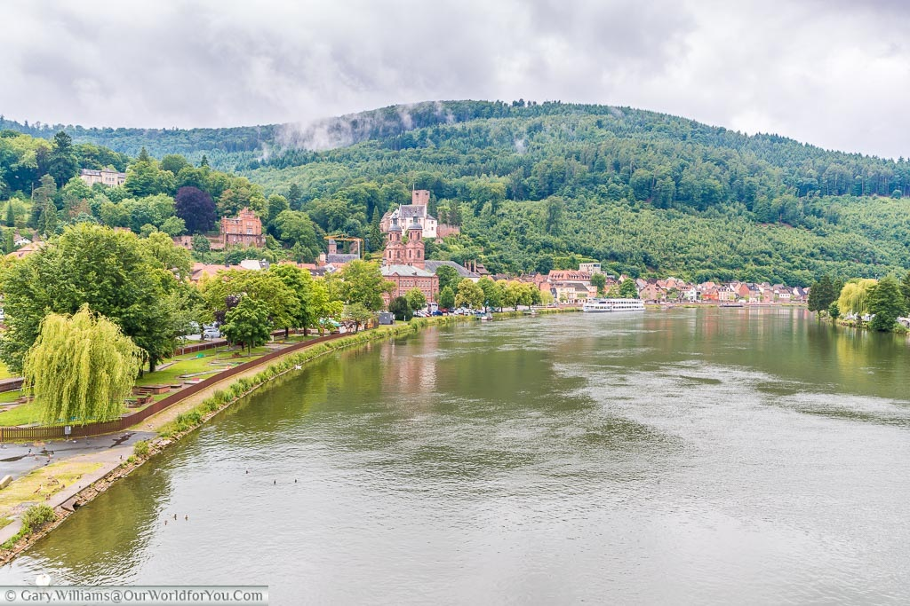 A view from a bridge over the River Main to the old Miltenberg town, with the wooded hillside in the background.