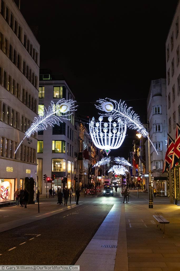 A view down New Bond Street in London's West End decorated with illuminated silver peacock feathers, and giant baubles above the junctions.