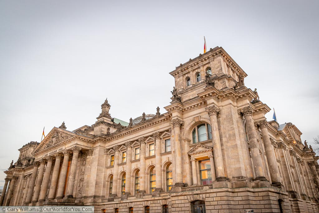 The grand neoclassical building that is the Reichstag.  tinged with an orange glow as dusk sets in.