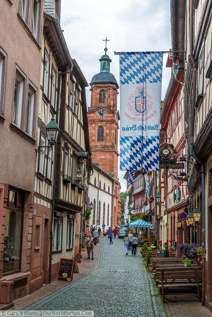 A cobbled street lined with bars and cafes and St Jakob's church bell tower in the background.  Outside one bar is a banner in the traditional blue and white check of Bavaria
