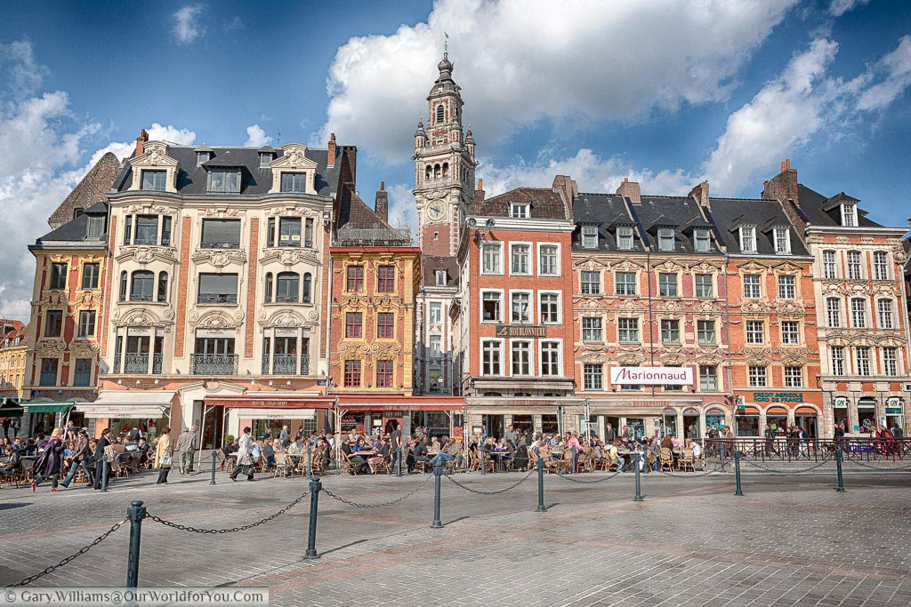 The scene of cafes that line the edges of Place Charles de Gaulle in Lille, northern France, underneath beautiful ornate buildings with the town's Clock tower in the background