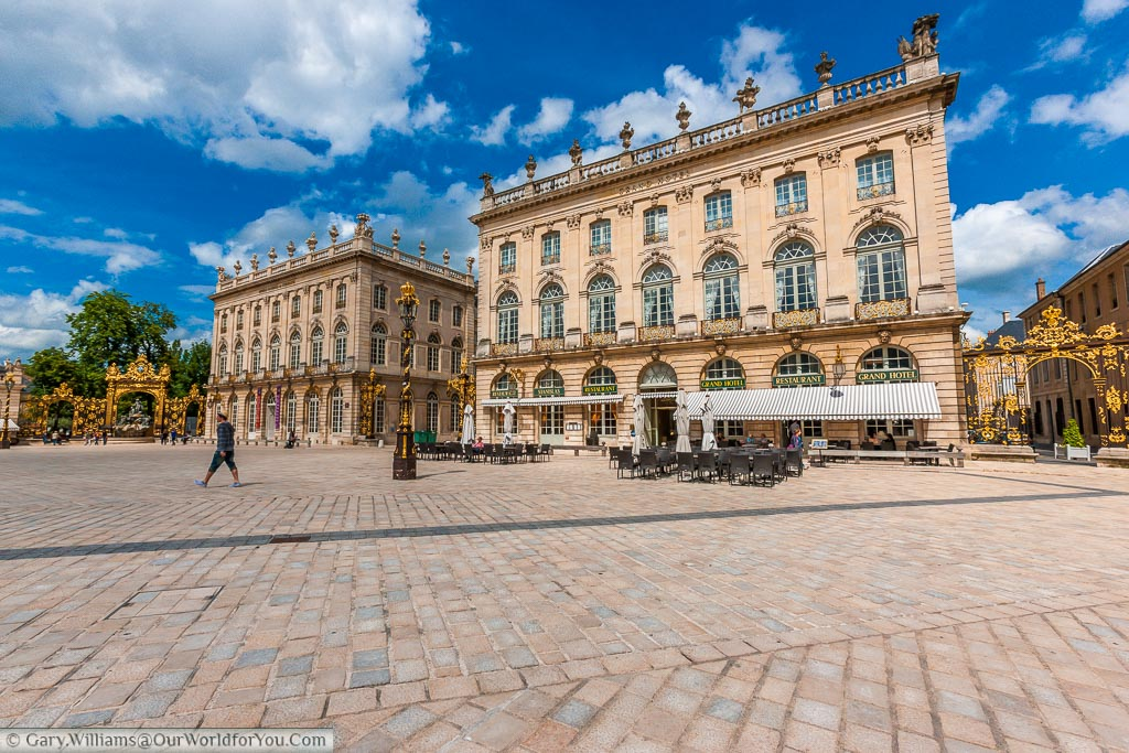 A view from the centre of the square Place Stanislas with three storey buildings with cafes at the bottom.  You can also see the black & gold wrought iron gates and lamp posts.