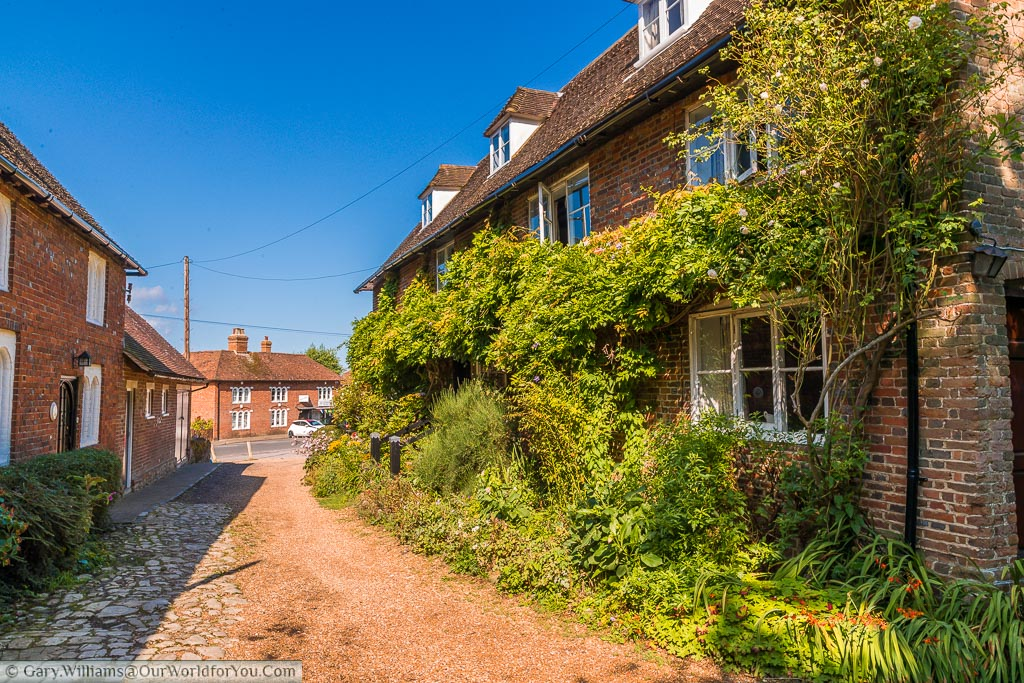 Gravel path leading from the church between 2 sets of cottages with one draped in wisteria on a beautiful summer's day.
