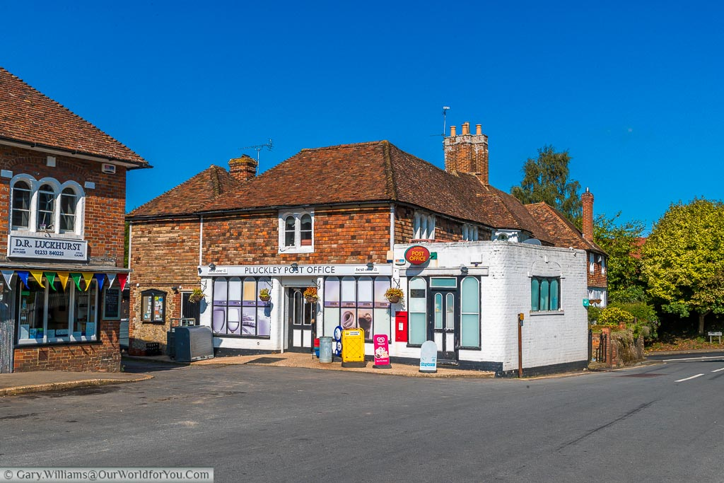A traditional butchers and post office in the village of Pluckley, Kent on a beautiful day under blue skies.