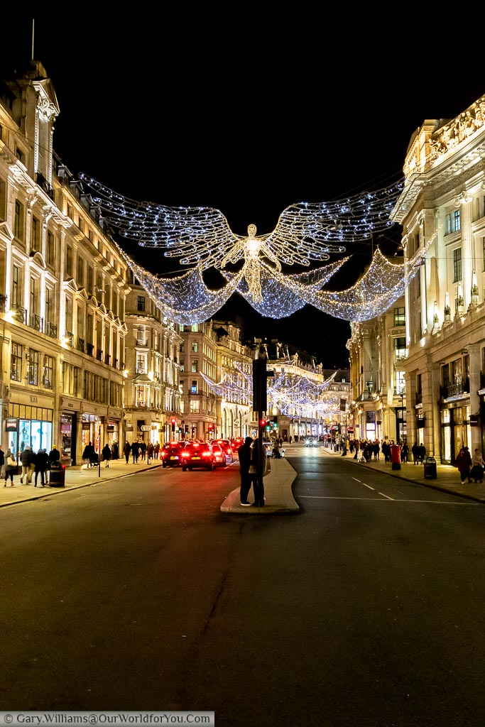 A view along Regent street with its illuminated Christmas Angels outstretched between either sides of the wide shopping street.