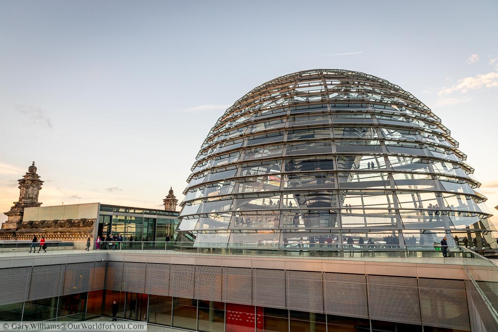 The view of the glass dome of the Reichstag in Berlin from the far corner of the rooftop walkway in the evening light.