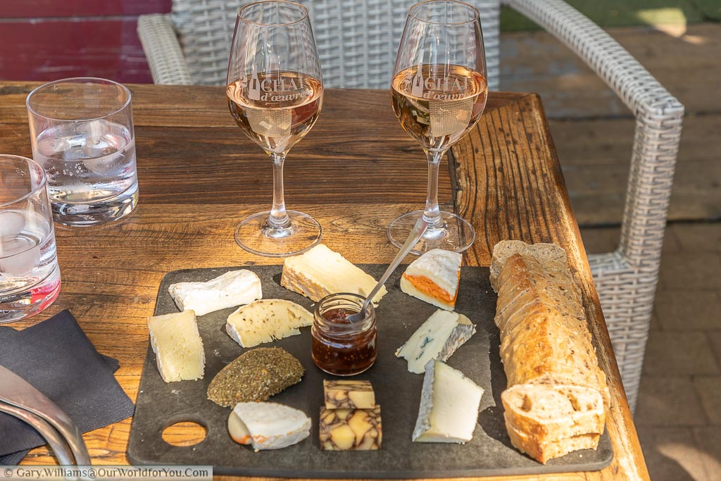 2 glasses of rose a wine and I cheese board with a selection of local produce  and fresh bread with the chutney in the center.