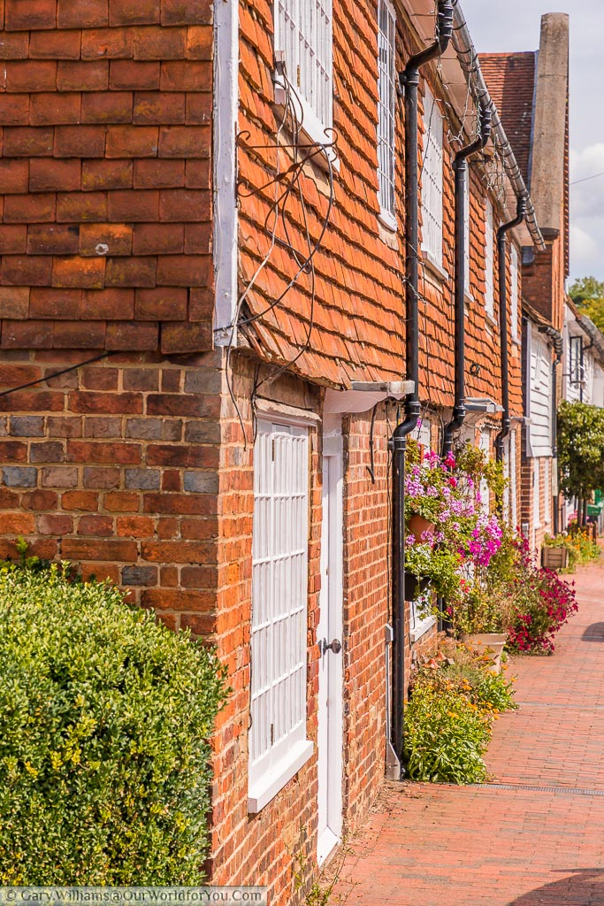 Looking along the High Street of Sissinghurst in Kent past beautifully decorated red brick homes