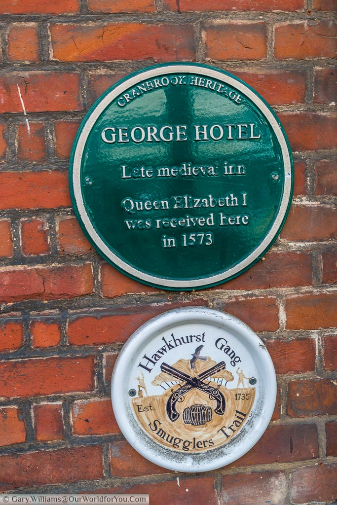 A green plaque from the Cranbrook Heritage society recognising the George hotel as a late medieval inn where Queen Elizabeth the 1st was received in 1573. A further plaque denotes the Hawkhurst Gang smuggler's trail.