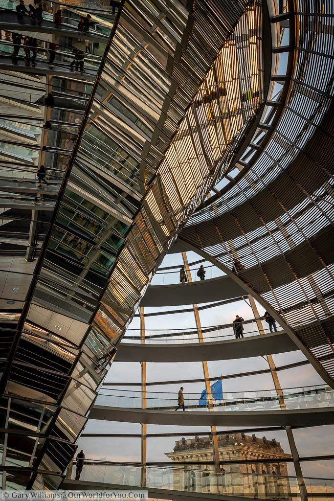Inside the dome of the Reichstag. A portrait view of the spiral staircase and the central inverted reflector the transfers  daylight down to the debating chamber below.