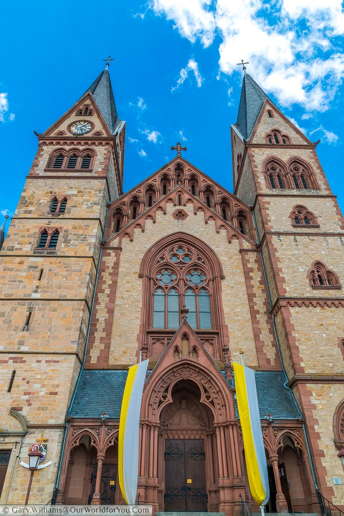 Looking up at the front of the Cathedral of Bergstraße with its yellow brickwork and deep red stonework.