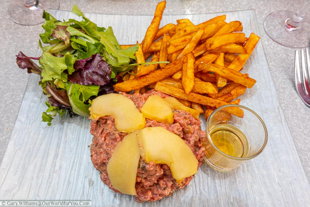 A plate of steak tartare served with a side salad and fried potatoes.  this dish has a regional twist in that is covered with poached apples and shot of calvados spirit on the side