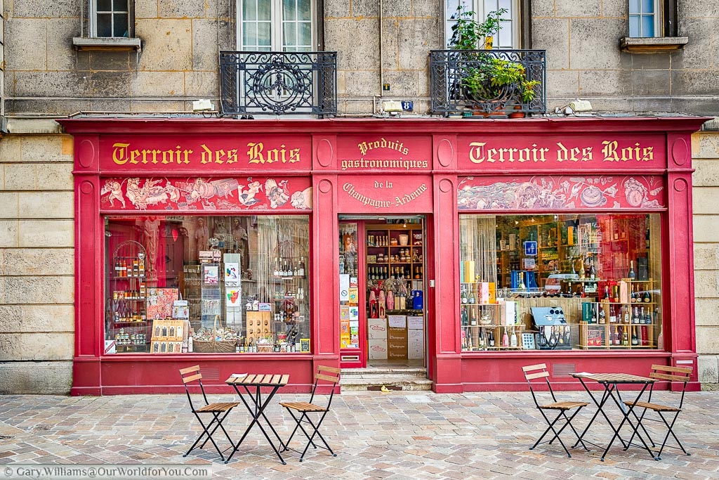 2 tables and chairs outside a gift shop painted in deep red, providing local gastronomic food produce from the Champagne-Ardenne region.  The shop is called Terroir des Rois which roughly translates I from the soil of Kings.