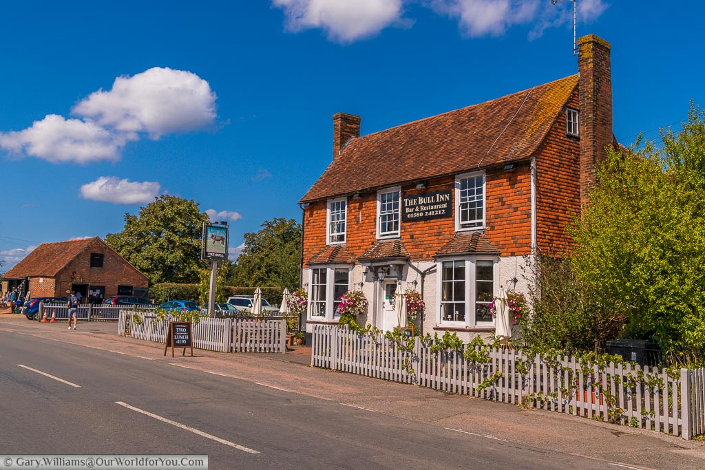 The Bull Inn, a traditional Kentish country pub with the picket fence and tables and chairs in its garden in Rolvenden, Kent