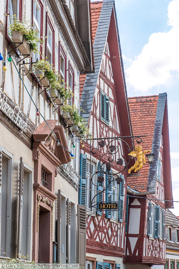 A roofline view of the gable ends of the building surrounding market platz.  Here you can see a wrought iron sign featuring Golden Angel of a local hotel.