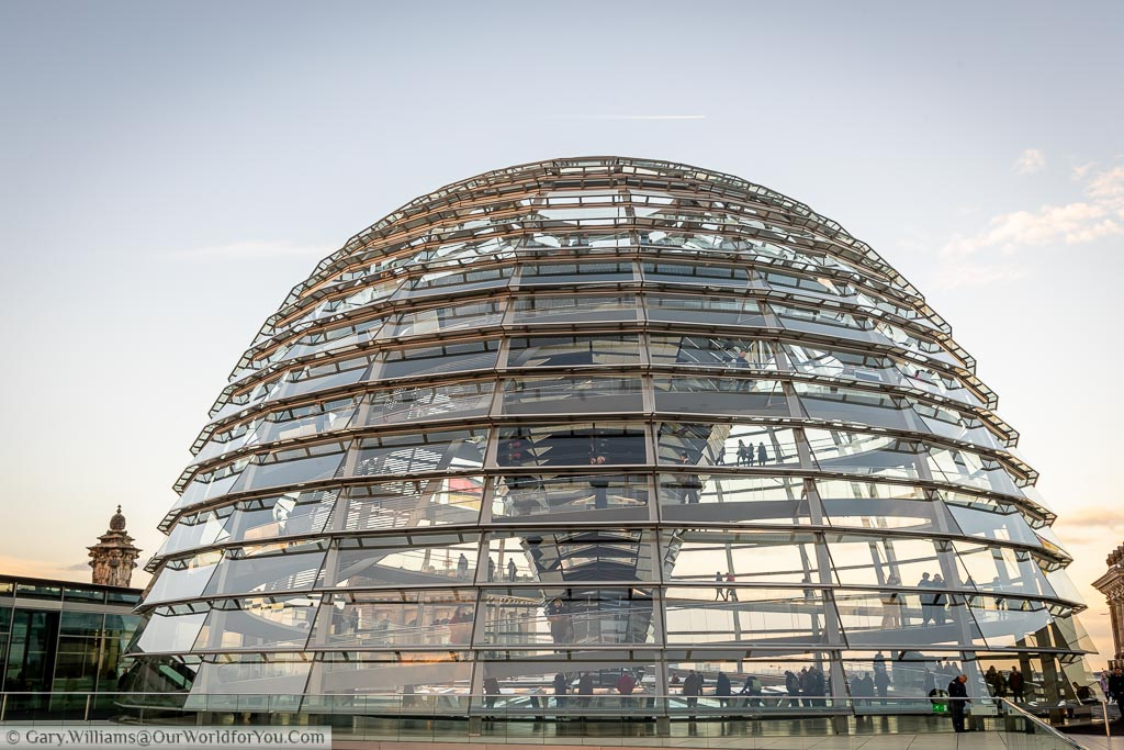 On the rooftop of the Reichstag in Berlin looking at the glass dome where you can see people walking up the spiral staircase to The viewpoint at the top.
