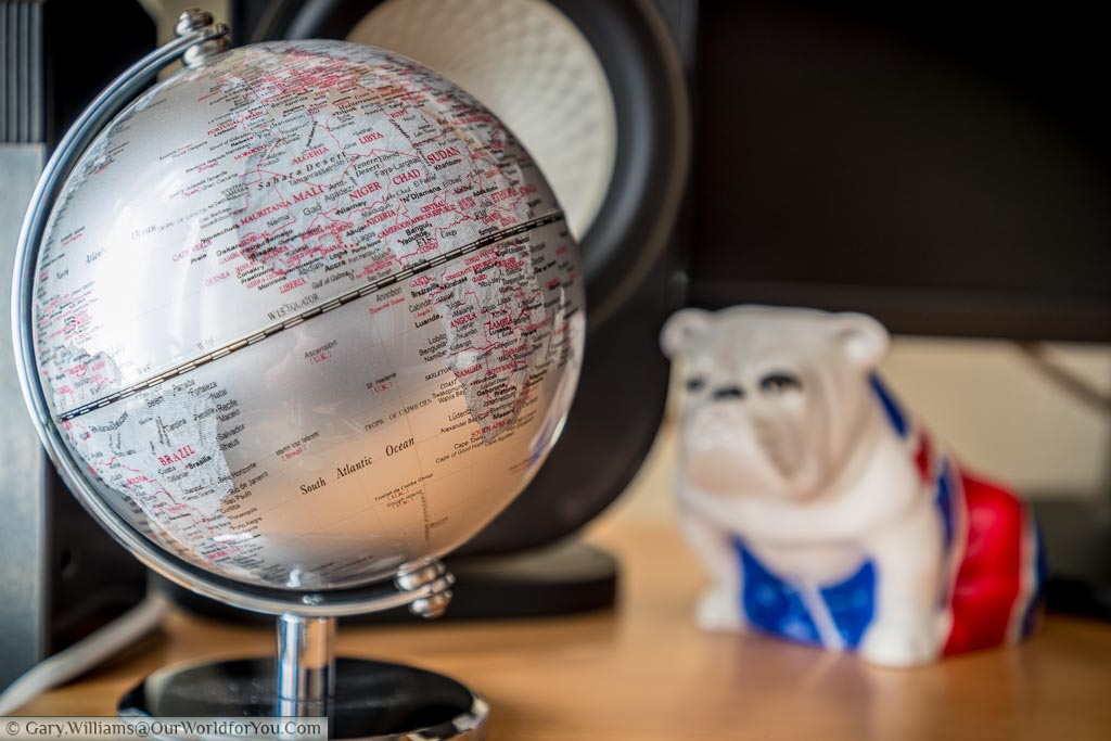 A silver small desktop globe with countries and borders highlighted in red. In the backgroud is the Royal Dalton Bulldog 'Jack' from the James Bond movie - Skyfall.