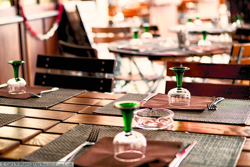 Tables and chairs at a cafe in the Alsace region of France with the distinctive green glass stemmed wine glasses synonymous with the area.