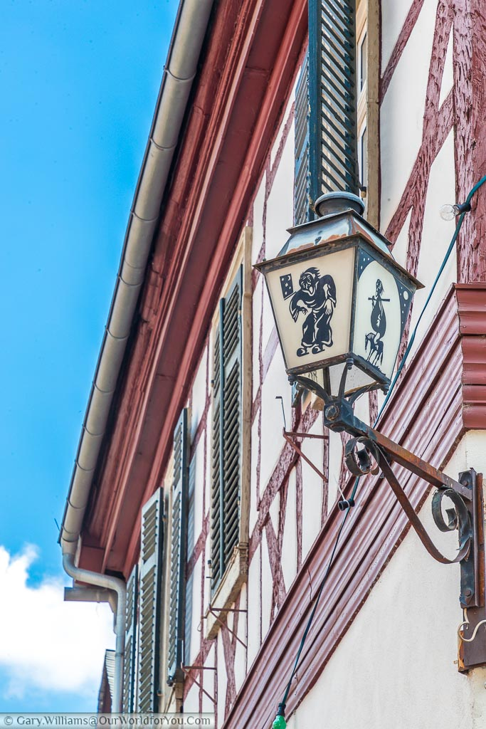 A close-up of a street Lantern attached to half-timbered building. The lantern depicts scene from local folklore.
