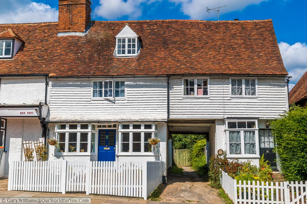 White picket fences in front of two traditional white weather boarded Kentish homes With the red tiled roof.  There is a driveway running between them wide enough for possibly a horse and cart.