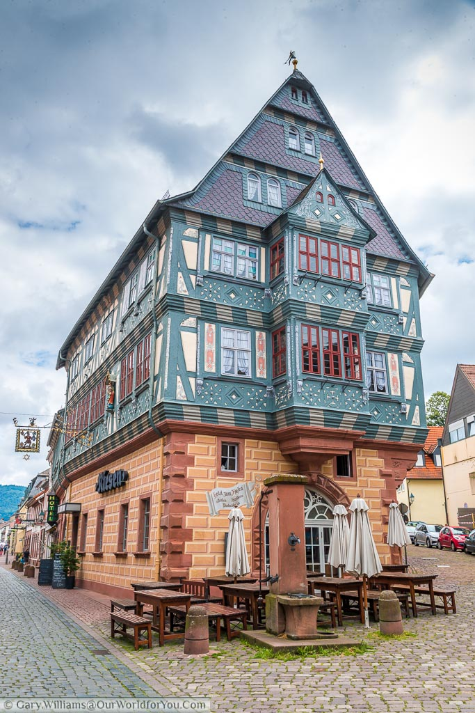 A restored Inn. The bottom half is red brick, the upper portion is half-timbered with blue woodwork and cream plaster.
