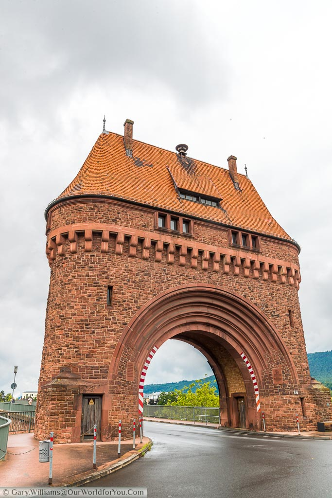 An impressive restored red brick archway supporting a watchtower above it, sits at the entrance to a bridge across the River Main