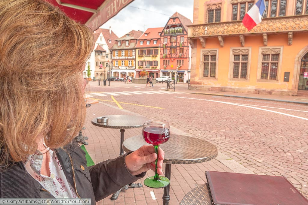 Janis holding a glass of pinot noir wine in Obernai, France. As is tradition in the region the wine glass has a green glass stem and a clear top.  She is overlooking the town square including the town hall displaying the French tricolore.