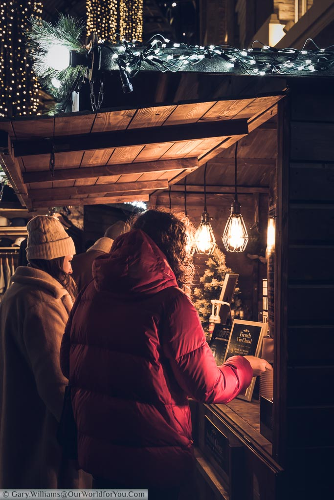 A group of ladies buying mulled wine from a wooden stall in Hay's Galleria