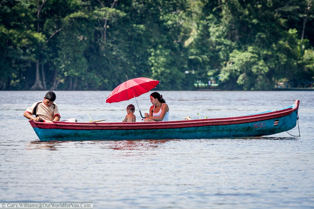 Small blue rowing boat on the water of Tortuguero , Costa Rica. There was a young fisherman with his wife holding a red umbrella shielding their young child from the midday sun.