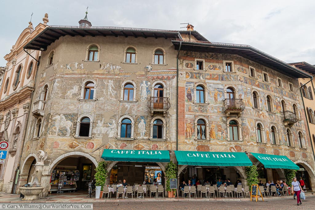 Café Italia in Piazza Duomo in the centre of Trento with green awnings covering the outdoor seating area with beautifully painted walls depicting classical Italian figures on the three storey renaissance building