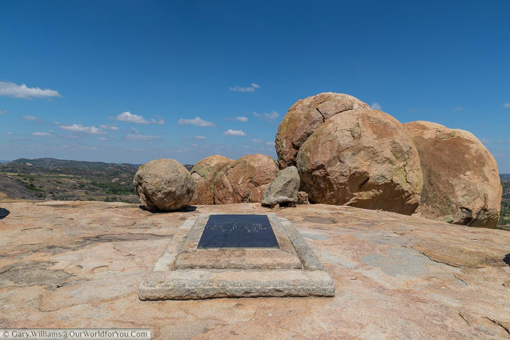 A full-size plaque over a stone marking the last resting place of Cecil John Rhodes on top of World's View in front of a collection of boulders.