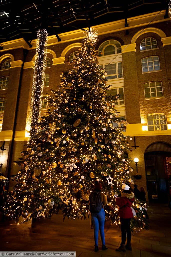 A couple of tourists in front of the huge Christmas tree in Hay's Galleria.