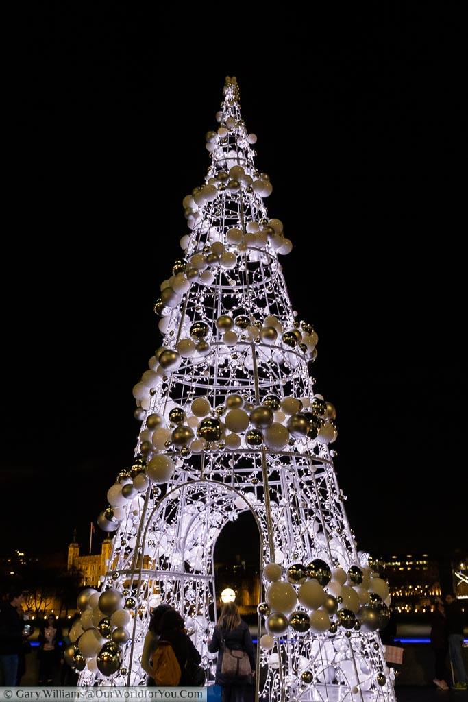 The Christmas Tree at London's City hall is a giant framework cone with a walkway through the centre illuminated with hundreds of white fairy lights, and a spiral of white & gold baubles from the top.