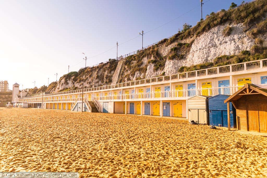 At the edge of the sands of Viking Bay is a row of beach cabins built into the cliff face. The doors of the cabins alternate between Bright yellow and a French blue