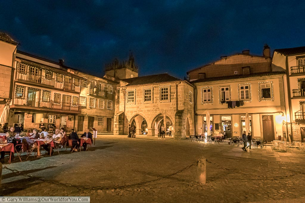 A lit square after dark in Guimarães, Portugal where diners sit at restaurants lining the square and others walkthrough the historical old town.