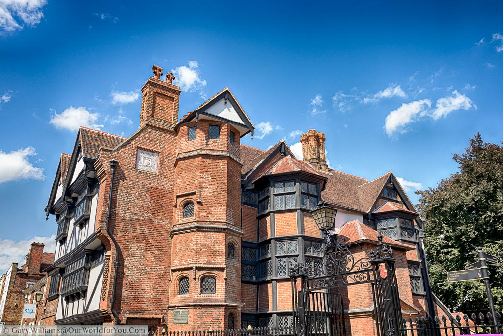 The historic Eastgate house in Rochester, A predominantly red brick building with heavy black framed windows and a Tudor style black and white frontage .