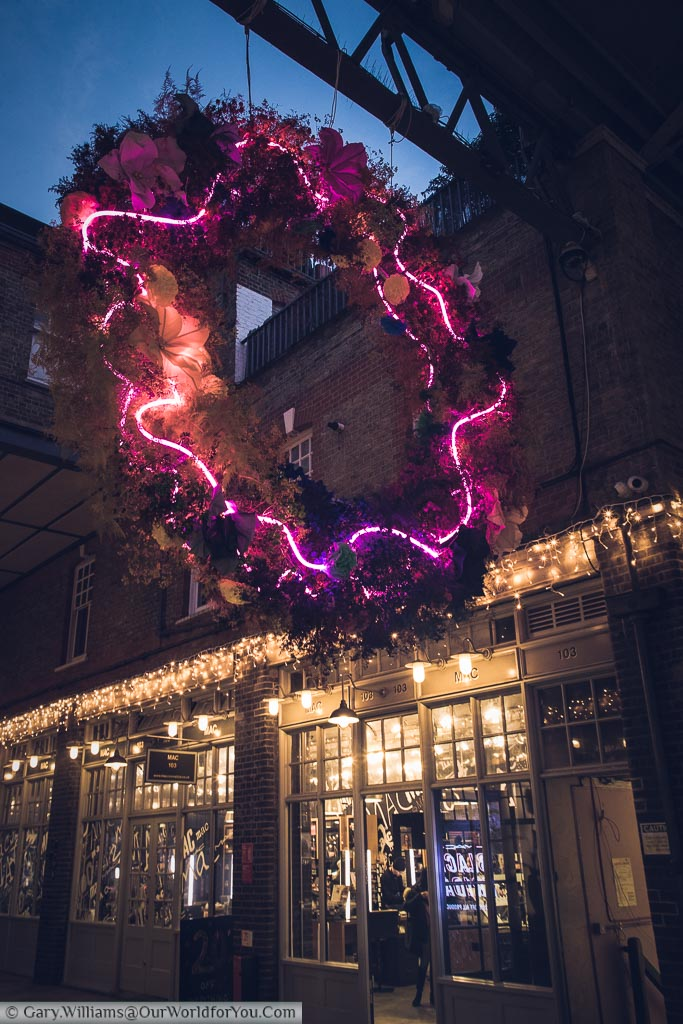 The giant festive wreath laced with pink neon fairy lights string adorns the entrance to Spitalfields market.