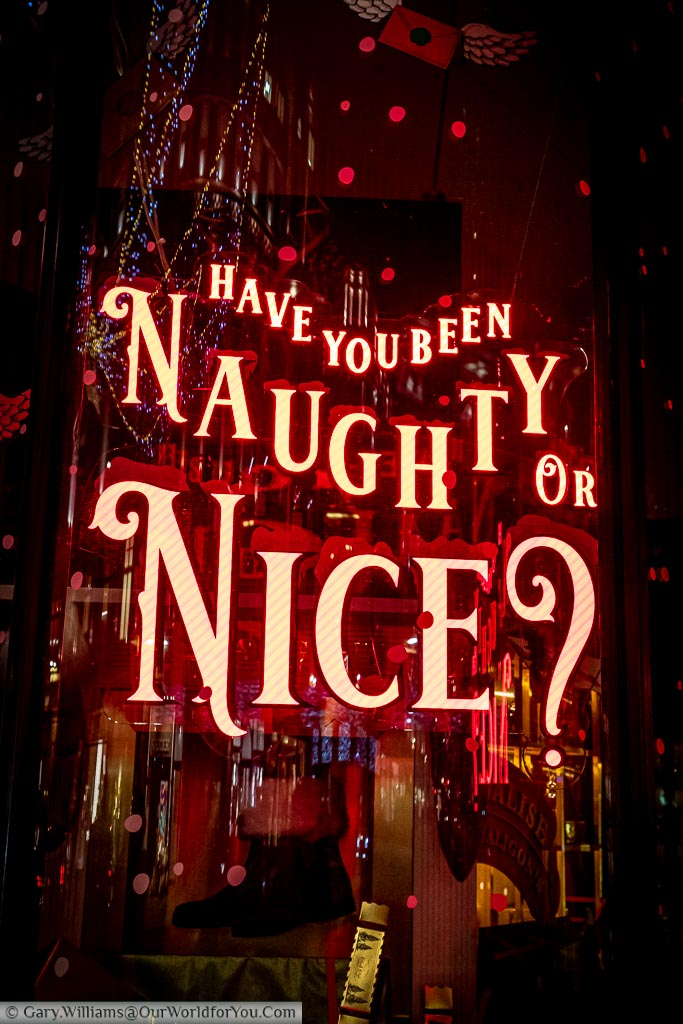 "A red neon sign in a shop window on Regent Street asking ""Have you been Naughy or Nice?"""