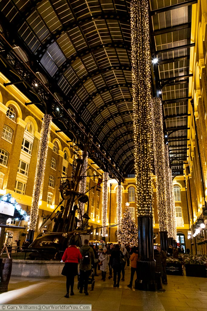 The view of Hay's Galleria at Christmas with its giant iron pillars decorated with fairy lights.