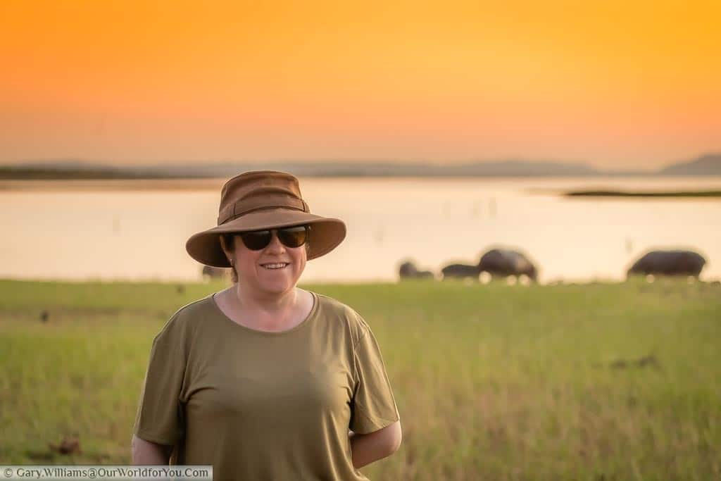 Janis at dusk besides an inlet on Lake Kariba with a herd of hippopotamus grazing at the water's edge