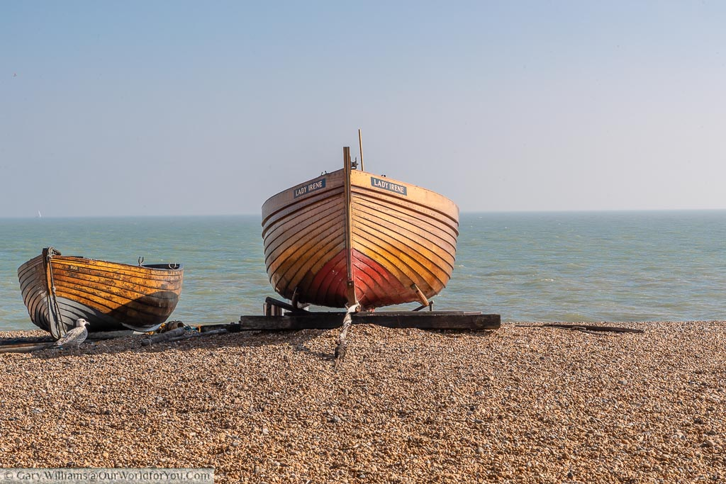 Two small varnished natural wood boats on the pebble beach of Deal in Kent in front of The English Channel