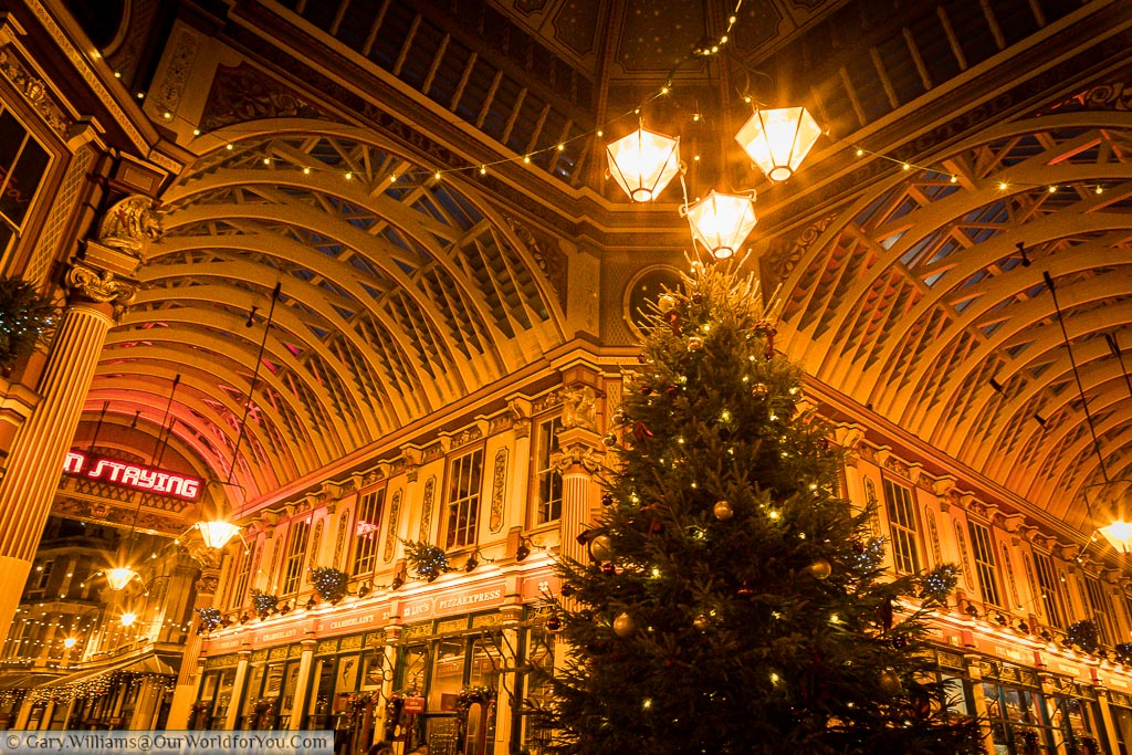 Inside the centre of Leadenhall Market at dusk, underneath the historic iron roof of this fabulous space.  The Christmas tree take centre stage under 3 bright Victorian lamps.