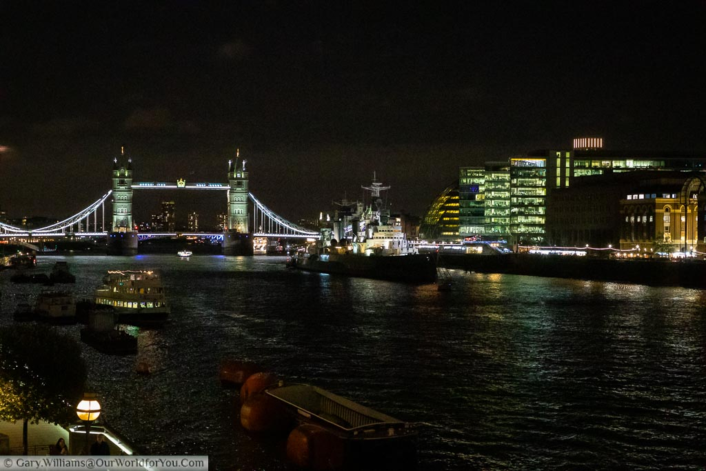 A view from London bridge across the River Thames to HMS Belfast, a large battleship and Tower Bridge and the Southside of the River which houses another Christmas market