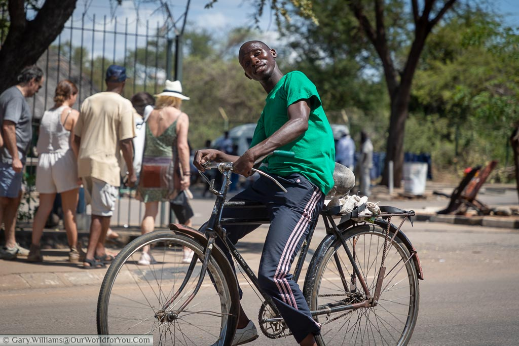 A young Zimbabwean posing for a photo as he rides by on a well-used old bicycle at Victoria Falls.