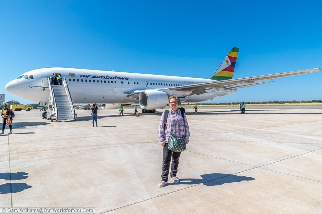 A casual Janis standing on the tarmac in front of the air Zimbabwe flight to Victoria Falls
