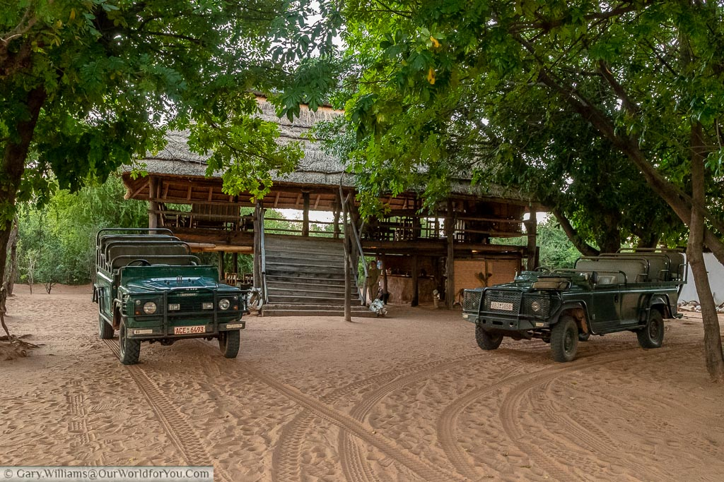 The two open topped safari Land Rovers parked in front of the Boma, or central gathering point, at the Rhino Safari Camp on Lake Kariba.